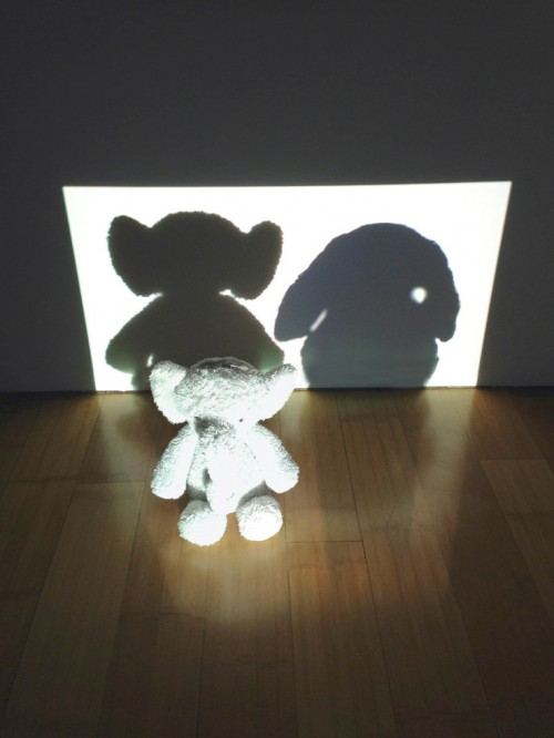 "Tobias Fike  ""Partial darkness or obscurity within a part of space from which rays from a source of light are cut off by an interpreted opaque body"" 2013 Projector, stuffed elephant, digital image 14 x 44 x 40 in. (35.6 x 111.8 x 101.6 cm)"